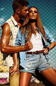 High fashion look.glamorbeautiful couple sexy stylish blond young woman model with bright makeup with perfect sunbathed skin and handsome muscled man in vogue style in jeans outdoors behind blue sky — Stock Photo