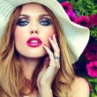 High fashion look.glamor closeup portrait of beautiful sexy stylish blond young woman model with bright makeup and pink lips with perfect clean skin in hat near summer flowers — Stock Photo #51799935