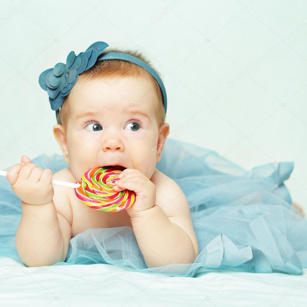 宝贝女孩穿着蓝色的衣服,吃棒棒糖– 图库图片