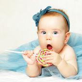 Baby girl eating lollipop — Stock Photo