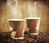 Paper cups with coffee beans — Stock Photo