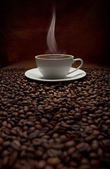 Cup of steaming coffee with beans — Stock Photo