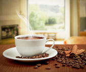 Cup of coffee with cinnamon and beans — Stock Photo