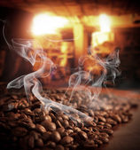 Roasted steaming coffee beans — Stock Photo