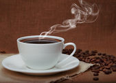 Steaming coffee on flax background — Stock Photo