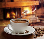 Hot coffee near fireplace — Stock Photo