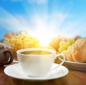 Sunny breakfast with coffee and fruits — Stock Photo
