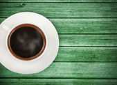 Cup of coffee on green wooden table — Stok fotoğraf