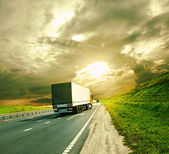 Trucks under colorful sky — Stock Photo