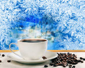 Hot coffee near frozen winter window — Stock Photo