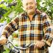 Old man riding bicycle — Stockfoto