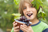 Happy boy wearing fresh grapes — Stock Photo