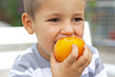 Little boy eating fresh fruit — Stock Photo