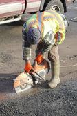 Labouer operating an asphalt cutting Tool — Stock Photo