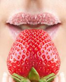 Woman's mouth with red strawberry covered with sugar — Stock Photo