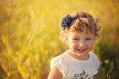 Smiling little girl on the field — Stock Photo