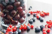 Blueberry, cherry and redcurrant in big glass — Stock Photo