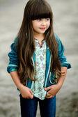 Portrait of little girl outdoors in denim jacket — Stock Photo