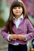 Portrait of little girl outdoors in a pink jacket — Stock Photo