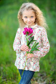 Portrait of little girl outdoors with peony — Stock Photo