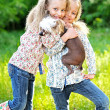Stock Photo: Portrait of two little girls twins with a dog