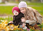 Portrait of two sisters in a park in autumn — Stock Photo
