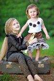 Retrato de duas irmãs em uma mala velha — Fotografia Stock