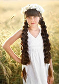 Portrait of a beautiful little girl in a field — Stock Photo
