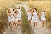 Portrait of little girls running on the field — Stok fotoğraf