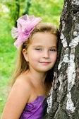 Portrait cute little girl standing near the tree — Stock Photo