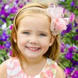 Outdoor portrait of cute little girl near the flowers - Photo