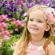 Outdoor portrait of cute little girl near the flowers - Stock Photo