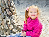 Outdoor portrait of cute sitting little girl — Stock Photo