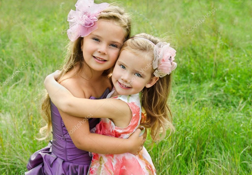 室外的两个拥抱可爱的小女孩的肖像– 图库图片