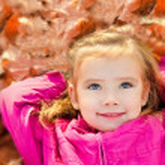 Portrait of cute little girl lying in leaves — Stock Photo #14079350