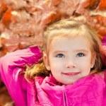 Portrait of cute little girl lying in leaves — Stock Photo