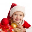 Little girl in christmas hat with gift box and balls — Stock Photo