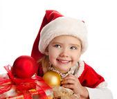 Kleines Mädchen in weihnachtsmütze mit Geschenkbox und Bällen — Stockfoto