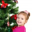 Stock Photo: Smiling cute little girl near the Christmas tree isolated
