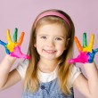 Smiling little girl with hands in the paint — Stock Photo #17647193