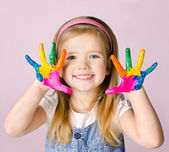 Smiling little girl with hands in the paint — Stock Photo
