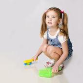 Cute little girl sweeps a floor — Stock Photo