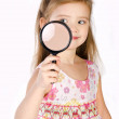 Beautiful little girl looking through a magnifying glass — Stock Photo #18922291