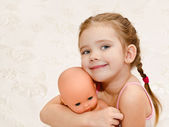 Cute smiling little girl with baby doll — Stock Photo
