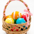 Colorful painted easter eggs in basket isolated — Stock Photo #21728009