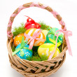 Colorful painted easter eggs in basket isolated — Stock Photo