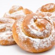 Stock Photo: Group of delicious cinnamon rolls icing sugar isolated