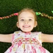 Stock Photo: Smililing happy little girl lying on grass