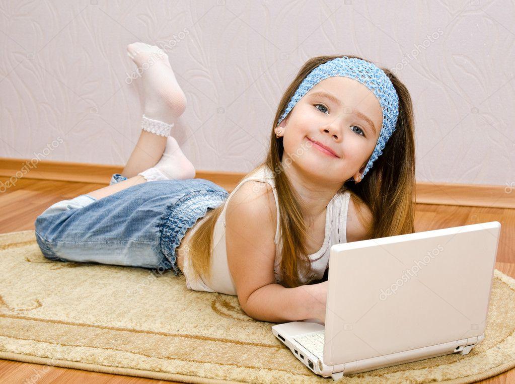 用一台笔记本电脑在家里地板上微笑着可爱的小女孩— 照片作者 sveta