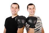 Twee aantrekkelijke jonge mannen tweeling in bokshandschoenen geïsoleerd glimlachen — Stockfoto